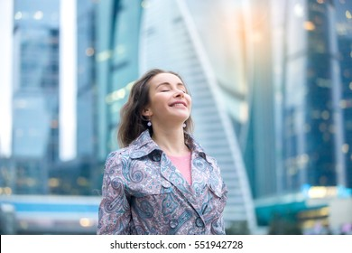 Portrait of young happy girl at street, her eyes closed with enjoyment, breathing at full outside. Lady feeling free, successful, ready to start day, visiting new town, blurred skyscraper background