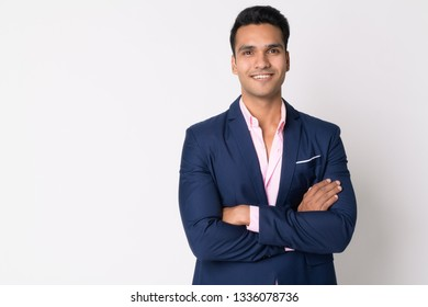 Portrait of young happy Indian businessman in suit smiling with arms crossed