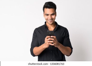 Portrait of young happy Indian businessman using phone