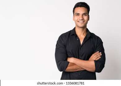 Portrait of young happy Indian businessman smiling with arms crossed