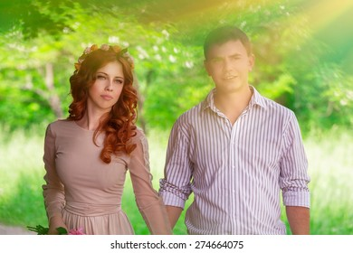 Portrait of young happy lovers walking in the park, spending wedding day outdoors, enjoying romantic date, love and tenderness concept