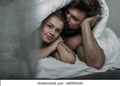 Portrait of young happy loving couple under blanket in bed