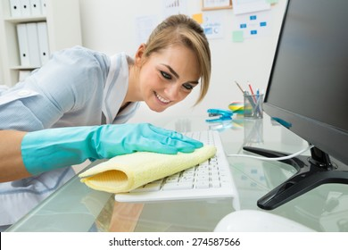 Portrait Of Young Happy Maid Cleaning Keyboard At Desk In Office