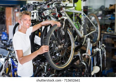 Portrait of young happy man buyer checking tire on bicycle wheel