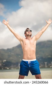 Portrait of a young happy man enjoying his vacation at the seaside, holding both hands in the air, laughing.