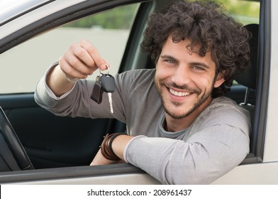 Portrait Of Young Happy Man Showing The Key Sitting In New Car