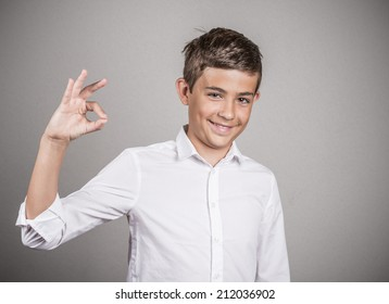 Portrait young happy man, teenager showing Ok sign, hand gesture, isolated grey wall background. Positive human emotions, facial expressions, nonverbal communication, body language, signs, symbols