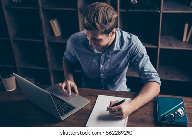 Portrait of young happy manager making notes and working with laptop