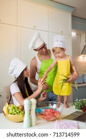Portrait of young happy parents who standing with cute little son in the kitchen in cook form, son keeping red pepper in hands and father biting it, mother keeping cauliflower and broccoli in hands