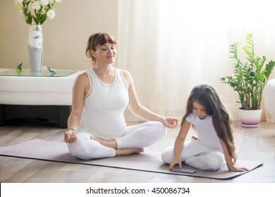 Portrait of young happy pregnant yoga mom spending time with her little daughter, meditating in lotus position with her kid girl playing games or using smart phone app in living room.