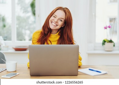 Portrait of young happy red-haired woman in yellow sweater using laptop