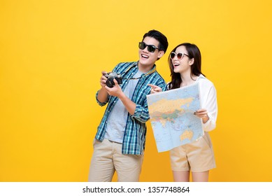 Portrait of a young happy smiling asian tourist couple in casual attire enjoying their summer vacation getaway together in yellow studio background