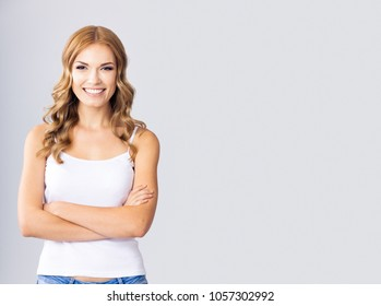 Portrait of young happy smiling blond woman, with empty copyspace area for text, slogan or advertising message, over grey background
