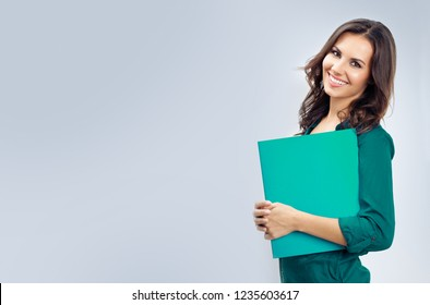 Portrait of young happy smiling business woman in green confident clothing with folder, empty copyspace place for slogan or some advertising text message, over grey background.