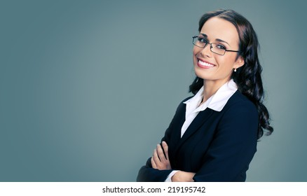Portrait of young happy smiling business woman in glasses, over gray background, with copyspace