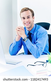 Portrait of young happy smiling businessman in blue shirt and tie at workplace. Success in business, job and education concept shot.