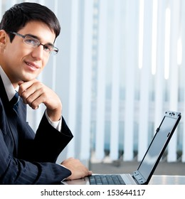 Portrait of young happy smiling businessman working with laptop at office