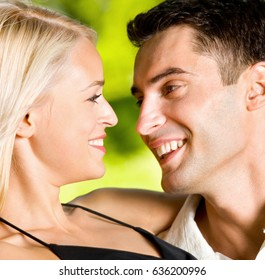 Portrait of young happy smiling cheerful embracing attractive couple together, outdoor. Love and relationships concept.
