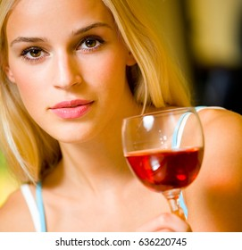 Portrait of young happy smiling cheerful beautiful blond woman with redwine