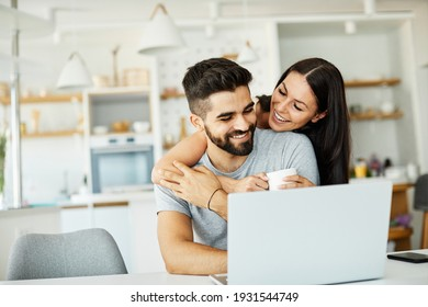 Portrait of a young happy smiling couple using laptop together at home. Wireless technology computer concept - Shutterstock ID 1931544749