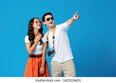 Portrait of a young happy smiling interracial tourist couple in casual attire enjoying their summer vacation getaway together in blue studio background