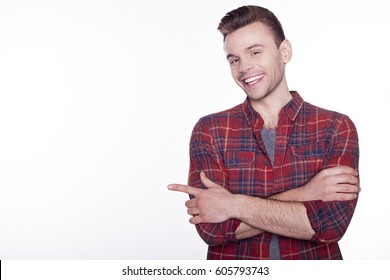A portrait of a young happy smiling man in checkered shirt isolated on white background poiting on copyspace.