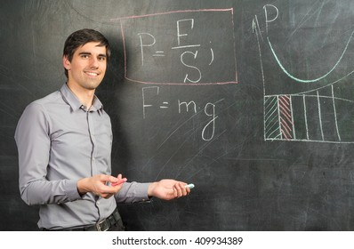 Portrait of young happy smiling teacher man standing near chalkboard with mathematical formulas
