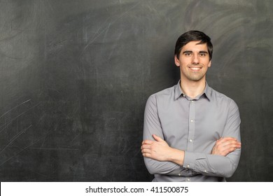 Portrait of young happy smiling teacher man standing near chalkboard background
