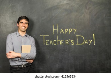Portrait of young happy smiling teacher man standing with book near chalkboard background with Happy Teacher's Day phrase on it