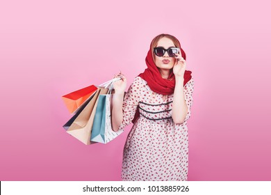 Portrait of young happy smiling woman with shopping bags on the pink Background.