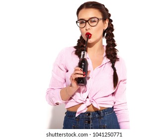 Portrait of young happy smiling woman model with bright makeup and red lips with two horns in summer colorful pink tied shirt drinking soda from glass bottle with straw, isolated on white