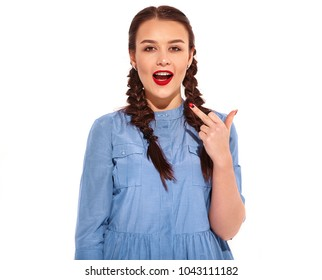 Portrait of young happy smiling woman model with bright makeup and red lips with two horns in hands in summer colorful blue dress and back pack isolated on white. Showing fuck off sign