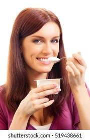 Portrait of young happy smiling woman eating yoghurt, isolated on white background. Healthy eating and vegetarian dieting concept studio shot.