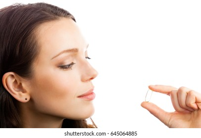 Portrait of young happy smiling woman showing Omega 3 fish oil capsule, isolated over white background. Healthcare and medicare concept shot.