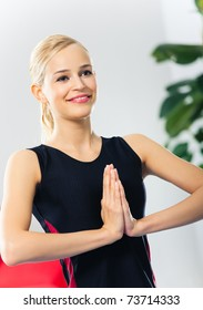 Portrait of young happy smiling woman in sportswear, doing fitness exercise, indoors