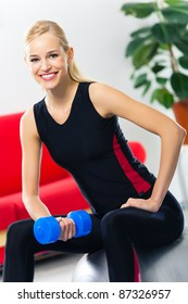 Portrait of young happy smiling woman in sportswear, doing fitness exercise with dumbbell on fit ball, at home