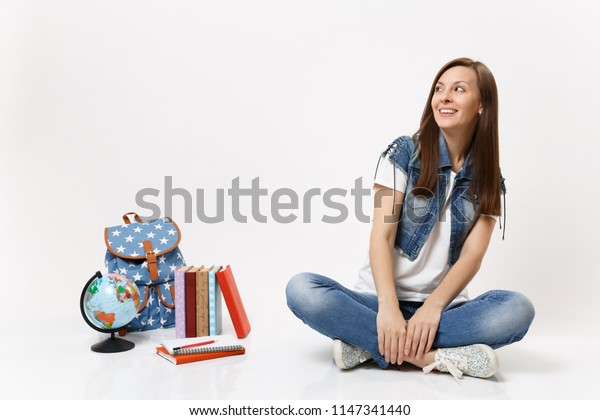 Portrait of young happy smiling woman student in denim clothes looking up, sitting near globe, backpack, school books isolated on white background. Education in high school university college concept