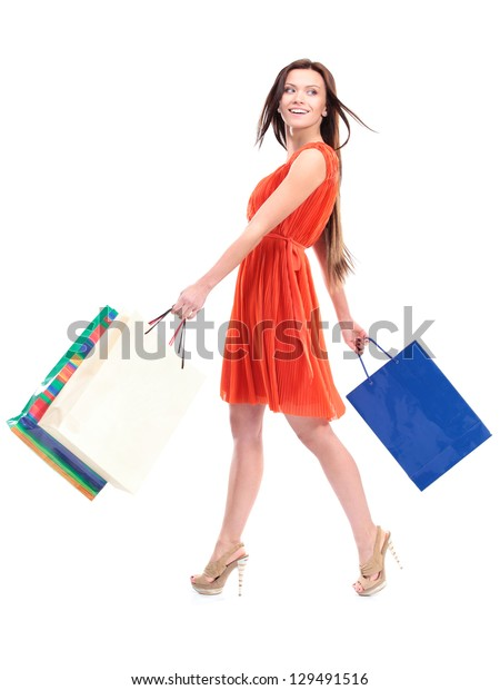 Portrait of young happy smiling woman with shopping bags, isolated over white background