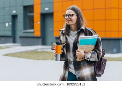 portrait of young happy student holding books coffee smiling after passing exams. Smart woman on university campus. College life. Teenanger in braces, eyeglasses with bag back to school. College life.