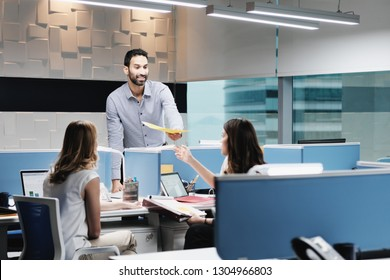 Portrait of young happy successful male manager in modern office. Busy hispanic business man smiling at work in executive coworking space with female colleagues working in team.
