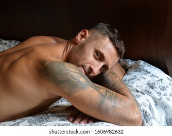Portrait of young happy tattooed man lying in bed.