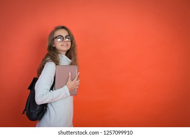 Portrait of young happy teenager girl holding tablet pc isolated on red background, study abstract, copyspace