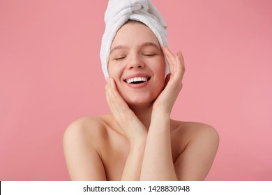 Portrait of young happy woman after shower with a towel on her head, broadly smiles with closed eyes, touches his face and smooth skin, stands over pink background