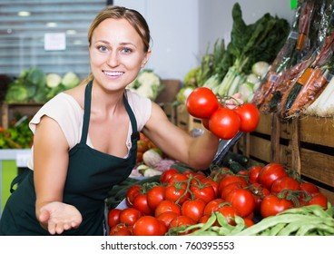 Portrait of young happy woman in apron selling organic tomatoes in shop