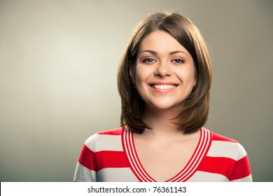 Portrait of young happy woman , big natural smile, beautiful model posing in studio over gray background . Isolated on gray. Light make-up without strong retouching natural skin.