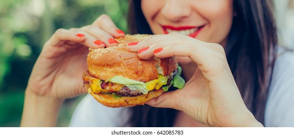 Portrait of a young happy woman eating tasty fast food burger
