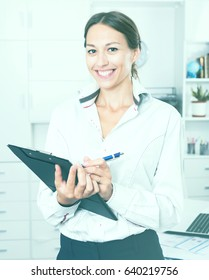 portrait of young happy woman in formal wear standing with folder with documents in office