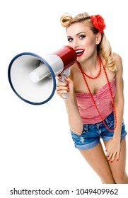 Portrait of young happy woman holding megaphone, dressed in pin-up style, blue jeans shorts, isolated against white background. Caucasian blond model posing in retro fashion vintage studio shoot.
