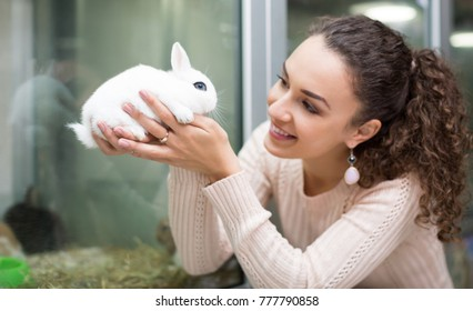 Portrait of young happy woman holding rabbit in hands