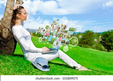 Portrait of young happy woman sharing her photo and video files in social media resources using her modern laptop. Outdoors at beautiful idyllic place.